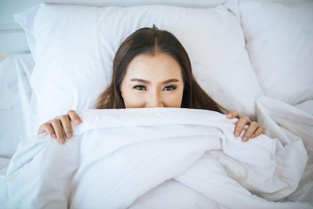 Piękna kobieta budzi się w łóżku, leniwy rano