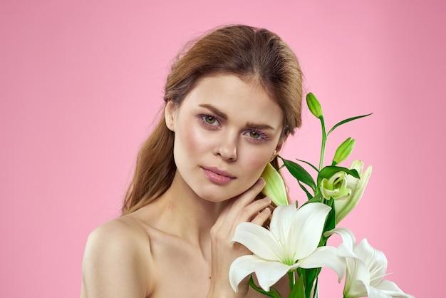 Piękna kobieta bukiet kwiatów kosmetyki nagie ramiona różowe.