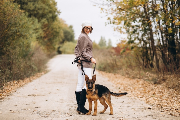Piękna kobieta chodzi jej psa w jesień parku out