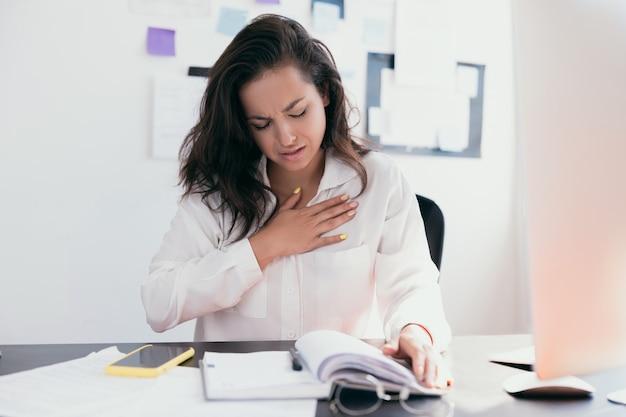 Piękna kobieta chora na ból w klatce piersiowej podczas pracy z papierami. ręka trzymająca klatkę piersiową po zażyciu leku.