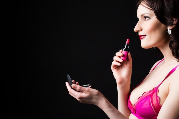 Piękna kobieta chwyt różowa pomadka odizolowywająca na czarnym tle.