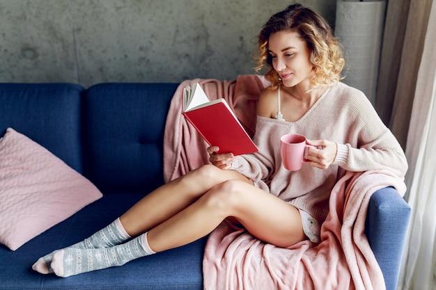Piękna kobieta, ciesząc się słoneczny poranek w domu, trzymając ulubioną książkę, pijąc kawę. ciepły, przytulny nastrój. różowe delikatne kolory.