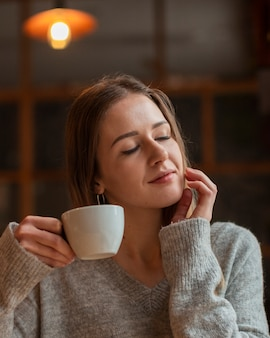 Piękna kobieta cieszy się filiżankę kawy