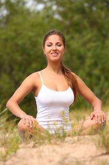 Piękna kobieta cieszy się joga przy lasem