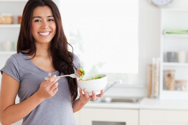 Piękna kobieta cieszy się puchar sałatka podczas gdy stojący