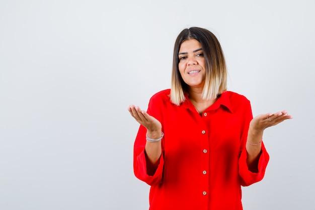 Piękna kobieta co gest pytanie pytanie w czerwonej bluzce i patrząc wesoły, widok z przodu.