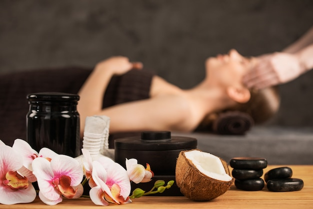 Piękna kobieta coraz masaż głowy w spa kwiaty orchidei kokos i kamienie