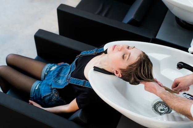 Piękna kobieta coraz mycia włosów w salonie piękności