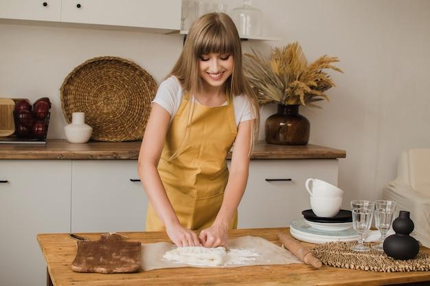Piękna kobieta cukiernik, piekarz lub gospodyni domowa w fartuchu ugniata ciasto w kuchni i uśmiecha się