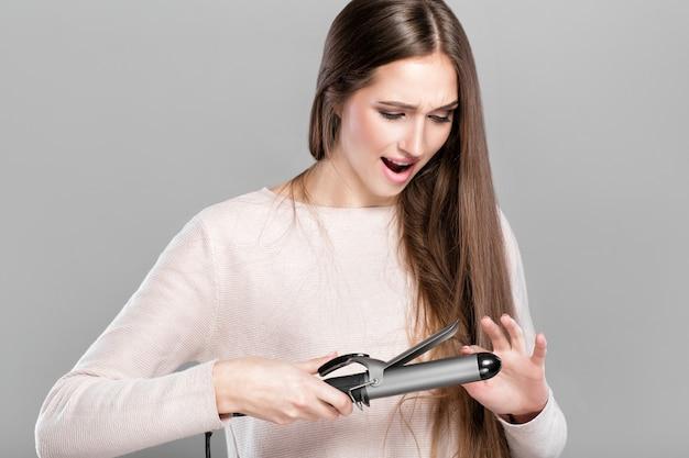 Piękna kobieta curling długie włosy za pomocą lokówki. dziewczyna spaliła sobie palec