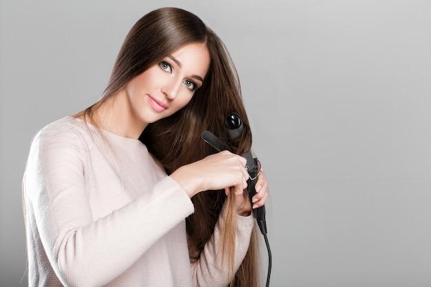 Piękna kobieta curling długie włosy za pomocą lokówki.
