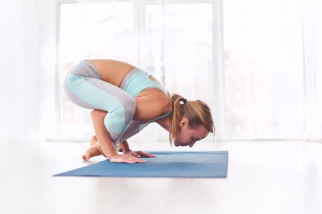 Piękna kobieta ćwiczy asana jogi bhuja pidasana