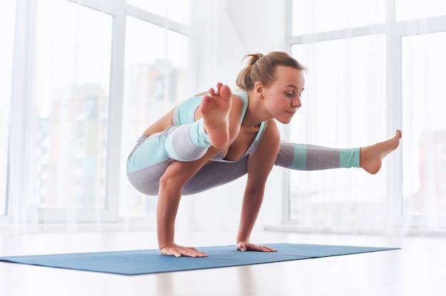 Piękna kobieta ćwiczy handstand joga asana tittibhasana - świetlik poza w studio jogi