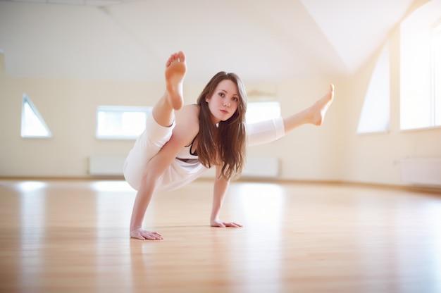 Piękna kobieta ćwiczy handstand joga asana tittibhasana. świetlik stanowią w studio jogi