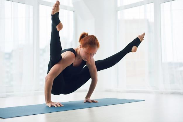 Piękna kobieta ćwiczy handstand joga asana tittibhasana
