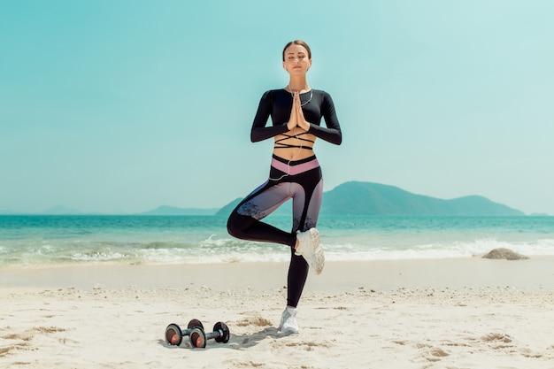 Piękna kobieta ćwiczy jogę nad morzem w słoneczny dzień. kobieta wykonuje ćwiczenia rozciągające. hantle leżące piasku.