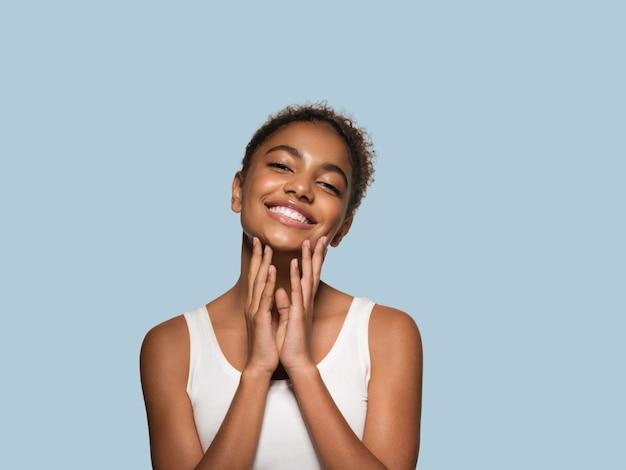 Piękna kobieta czarna skóra twarz uśmiechający się model dotykając jej twarzy. kolor tła. niebieski