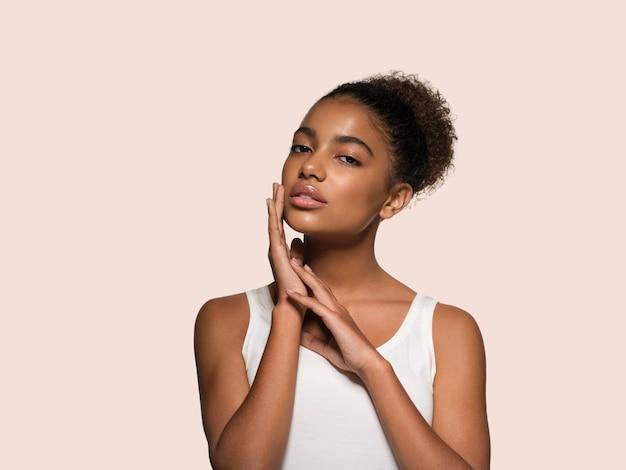 Piękna kobieta czarna skóra twarz uśmiechający się model dotykając jej twarzy. kolor tła. różowy