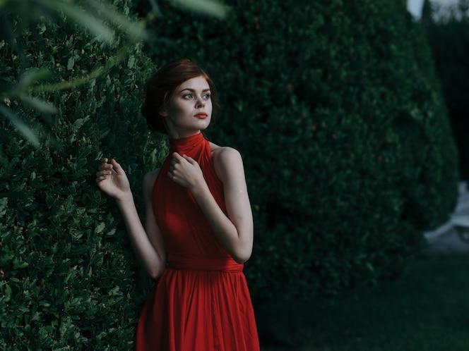 piękna kobieta czerwona sukienka kosmetyki atrakcyjny wygląd zielony krzak karnawał