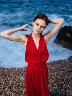 Piękna kobieta czerwona sukienka luksusowy krajobraz skalisty kamień.
