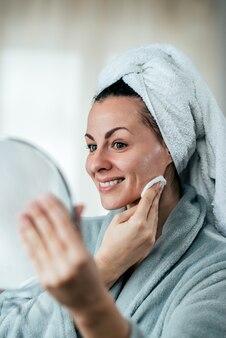 Piękna kobieta czyści jej twarz z bawełnianym ochraniaczem, trzyma lustro.
