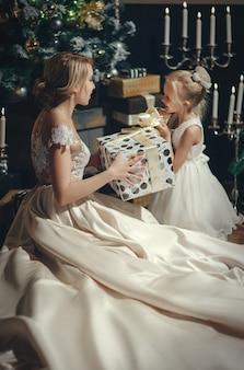 Piękna kobieta daje prezent dla małej dziewczynki