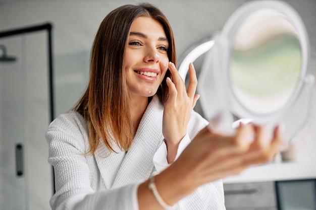 Piękna kobieta dba o jej twarz