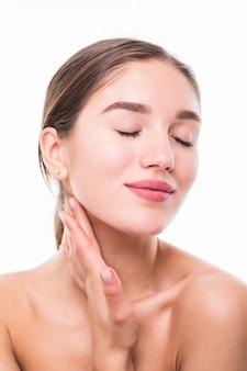 Piękna kobieta dba o skóry twarzy pozuje przy studiiem odizolowywającym na biel ścianie