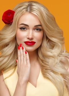 Piękna kobieta długie kręcone blond włosy kwiat w włosy wypielęgnowane paznokcie. modne kolory pomarańczowy i żółty