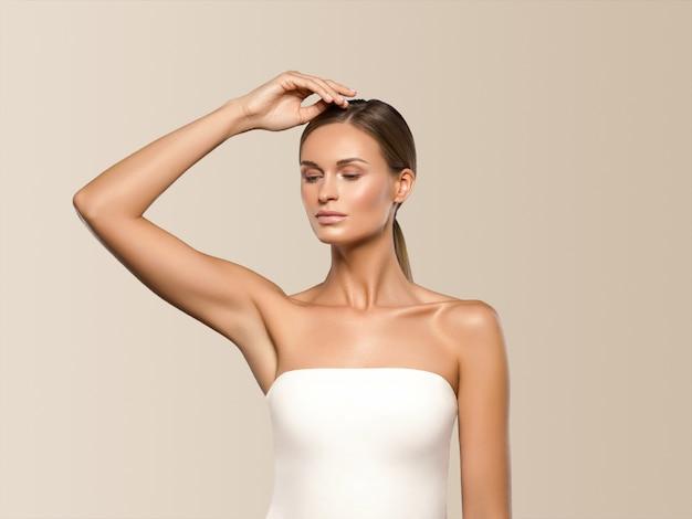 Piękna kobieta długie włosy blond naturalny portret z makijażem uroda. na beżu.