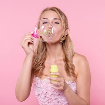 Piękna kobieta dmuchanie balonów na imprezie