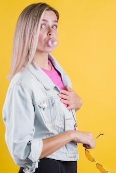 Piękna kobieta dmuchanie gumy do żucia