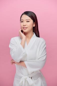 Piękna kobieta do pielęgnacji skóry dotyka jej podbródka i uśmiechu