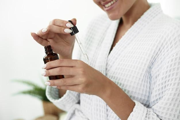 Piękna kobieta do pielęgnacji skóry upuszczanie kolagenu na rękę w łazience.