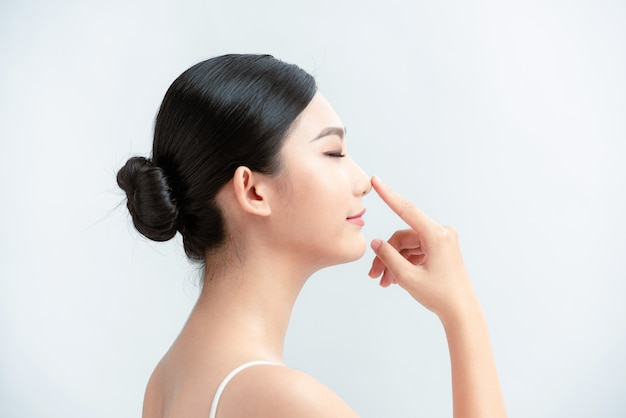 Piękna kobieta do pielęgnacji skóry uśmiecha się radośnie i wskazuje nos na białej ścianie