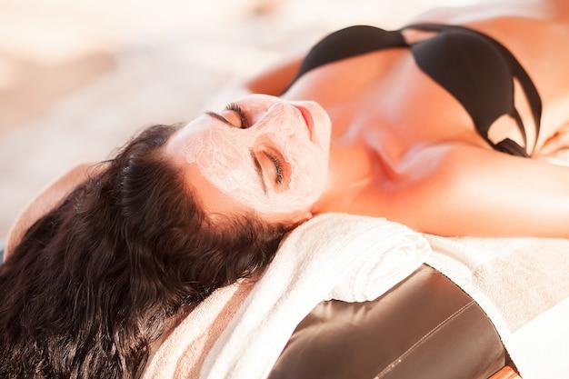 Piękna kobieta dostaje maskę spa na słonecznej plaży w salonie spa na świeżym powietrzu