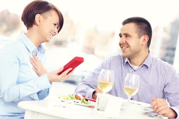 Piękna kobieta dostaje prezent od męża w restauracji