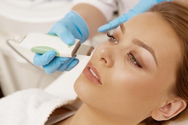 Piękna kobieta dostaje ultradźwięk twarzowy przy piękno kliniką
