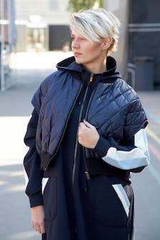 Piękna kobieta, dziewczyna stoi przy ścianie w mieście w kurtce
