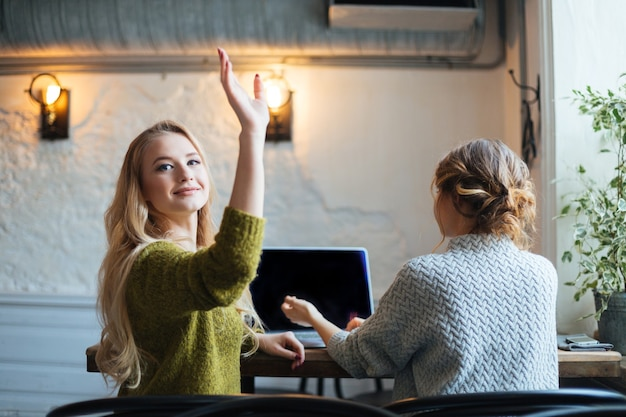 Piękna kobieta dzwoni do kelnera w kawiarni