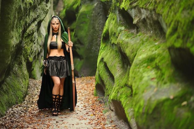 Piękna kobieta elf łucznik w lesie polowanie z kokardą