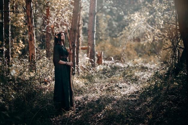 Piękna kobieta elfa, bajkowy las z długimi uszami, długie ciemne włosy złote wieńce na głowie