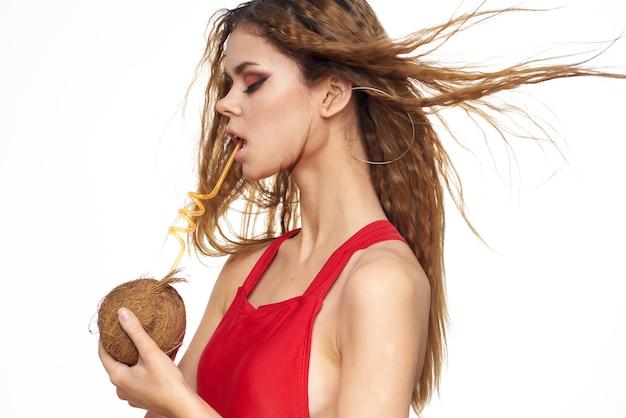 Piękna kobieta falowane włosy kokosowy koktajl w ręce, ciesząc się latem styl życia jasnym tle