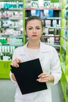 Piękna kobieta farmaceuta trzymająca w rękach schowek