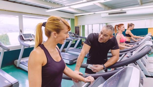 Piękna kobieta fitness na bieżni rozmawia z przystojnym mężczyzną w centrum fitness