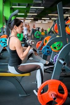 Piękna kobieta fitness podnoszenia brzana. sportowa kobieta podnoszenia ciężarów. fit dziewczyna ćwiczenia mięśni budynku. kulturystyka fitness