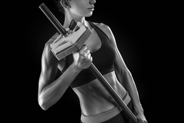 Piękna kobieta fitness przygotowuje się do podnoszenia ciężkich ciężarów, czarno-białe zdjęcie