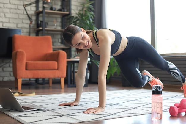 Piękna kobieta fitness robi ćwiczenia alpinistów oglądając samouczki online na laptopie, trening w salonie. zdrowy tryb życia. dziewczyna uprawia sport w domu.