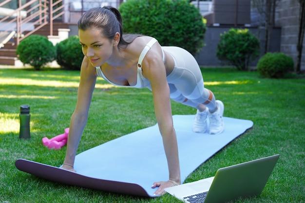 Piękna kobieta fitness robi ćwiczenia deski oglądając samouczki online na laptopie, szkolenia na świeżym powietrzu. zdrowy tryb życia. dziewczyna idzie na sport w ogrodzie.
