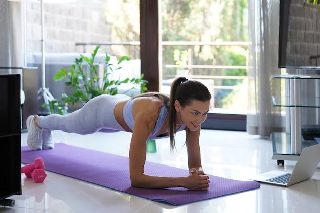 Piękna kobieta fitness robi ćwiczenie deski oglądając samouczki online na laptopie, szkolenie w salonie. zdrowy tryb życia. dziewczyna uprawia sport w domu.